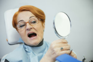 woman looking in mirror at dentist